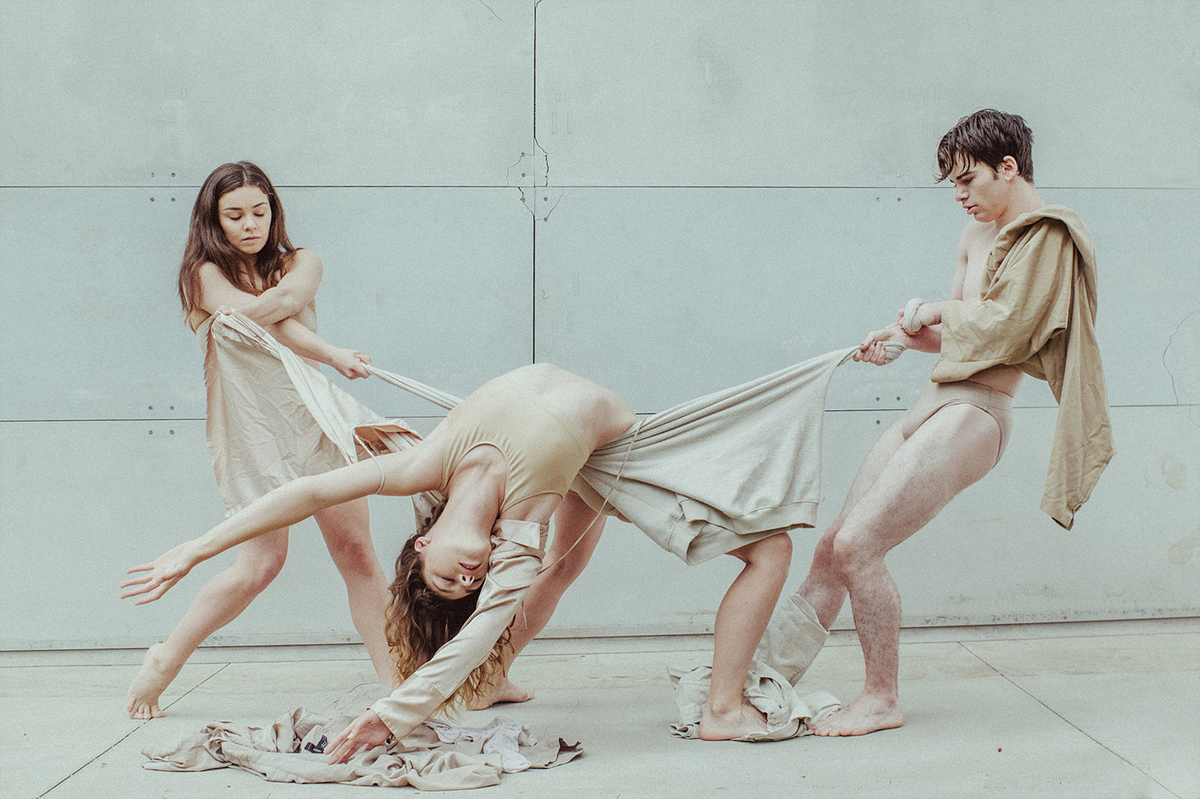 three dancers tangled in nude clothes