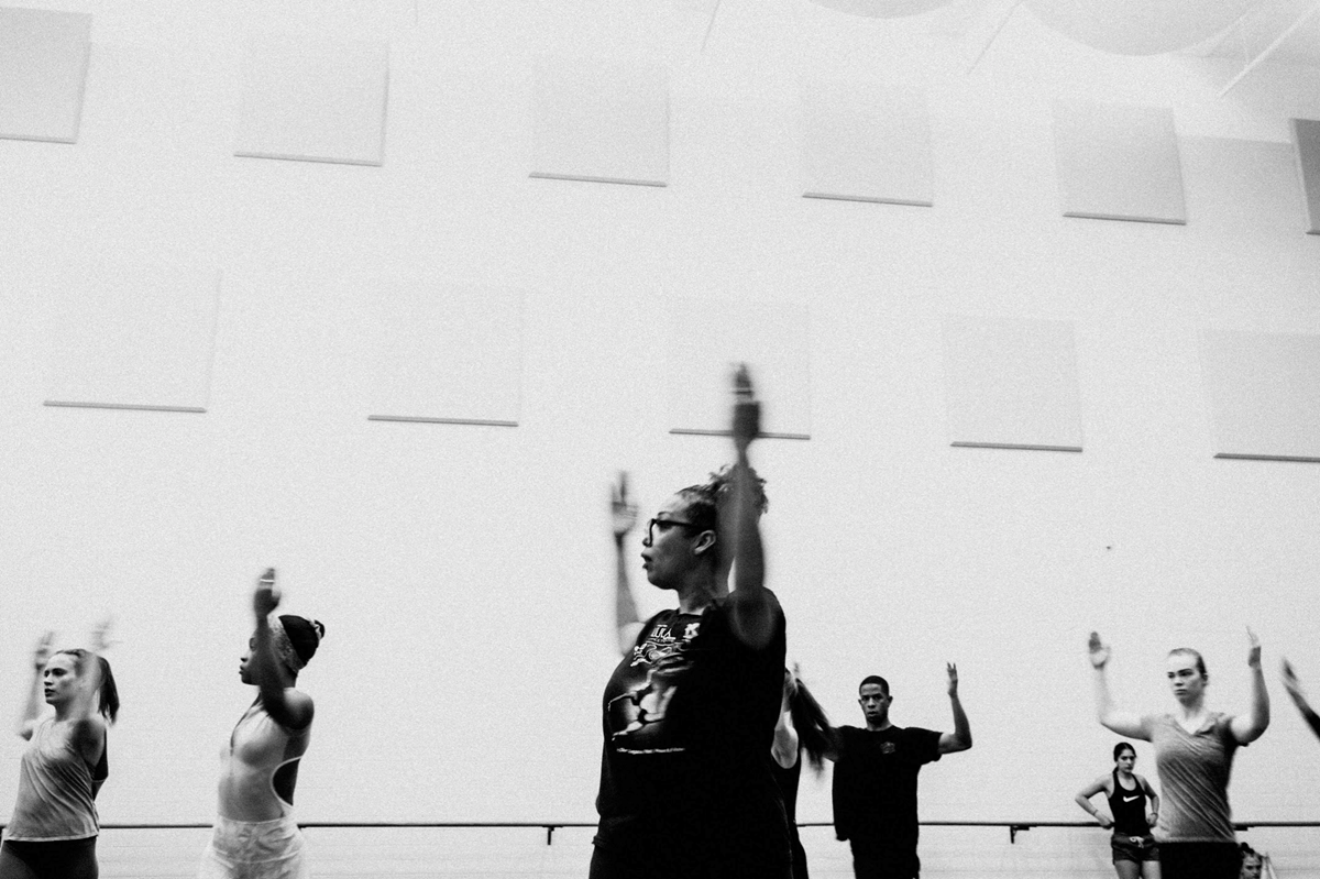 Dancers with arms above head in cactus position in technique class
