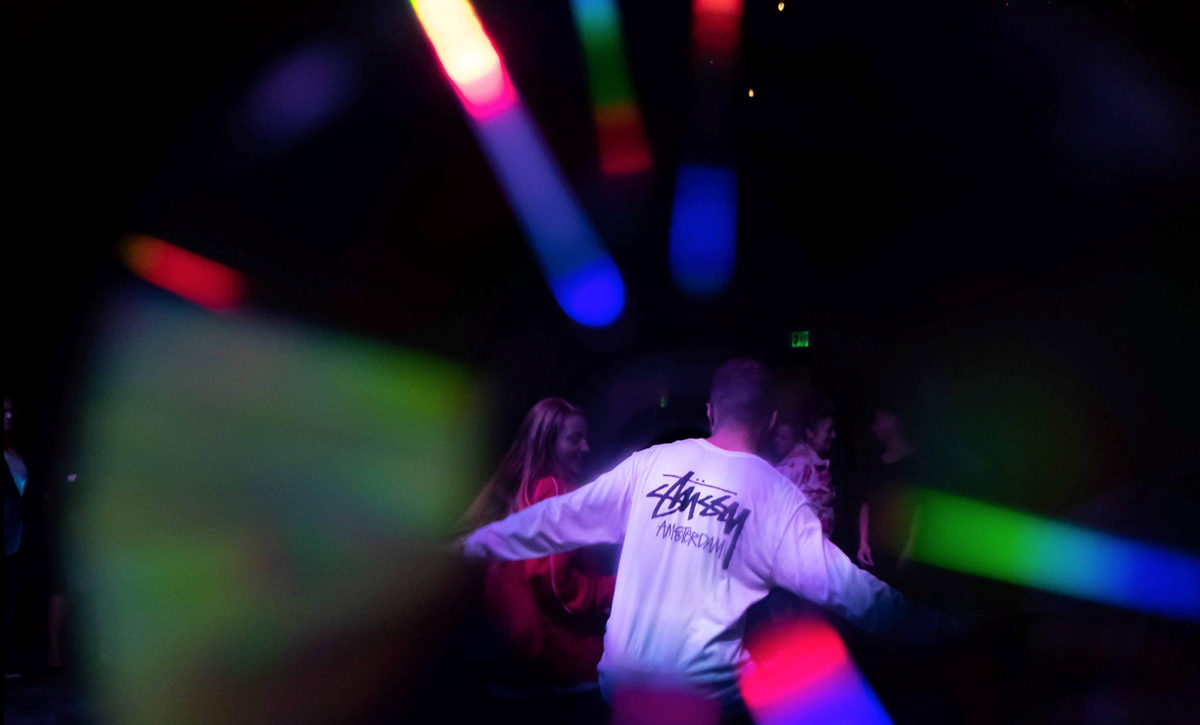Students dancing with a rainbow flare